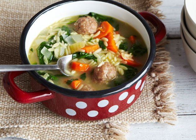 A pot of soup with meatballs and veggies