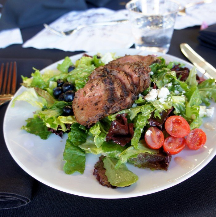 A plate with a white plate with sliced beef on a bed of lettuce and veggies