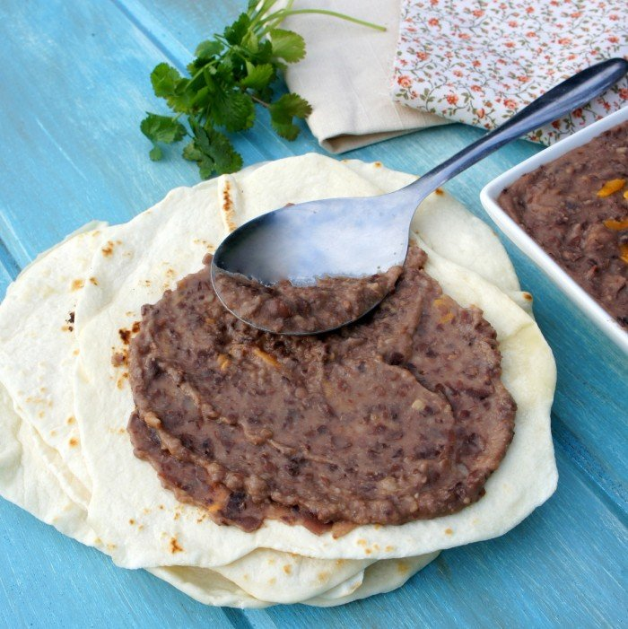 A spoon spreading refried beans on a tortilla