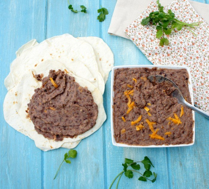A square bowl of refried beans topped with cheese next to a small pile of tortillas with refried beans spread on one