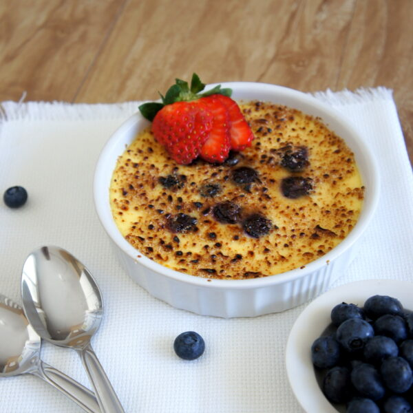A Blueberry Cheesecake Creme Brûlée topped with a sliced strawberry
