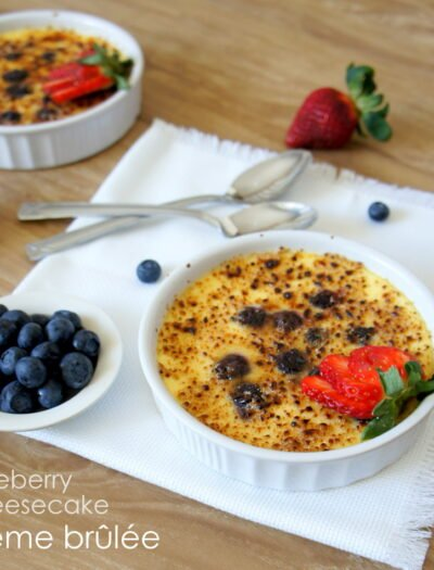 A bowl of Blueberry Cheesecake Creme Brûlée displayed on a table next to a bowl of blueberries