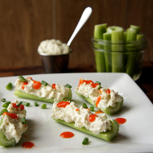 A plate with celery sticks filled with Creamy Buffalo Blue Cheese