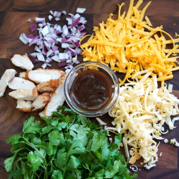 A wooden surface with chopped onions, shredded cheese, cilantro, chopped chicken surrounding a small bowl of BBQ sauce