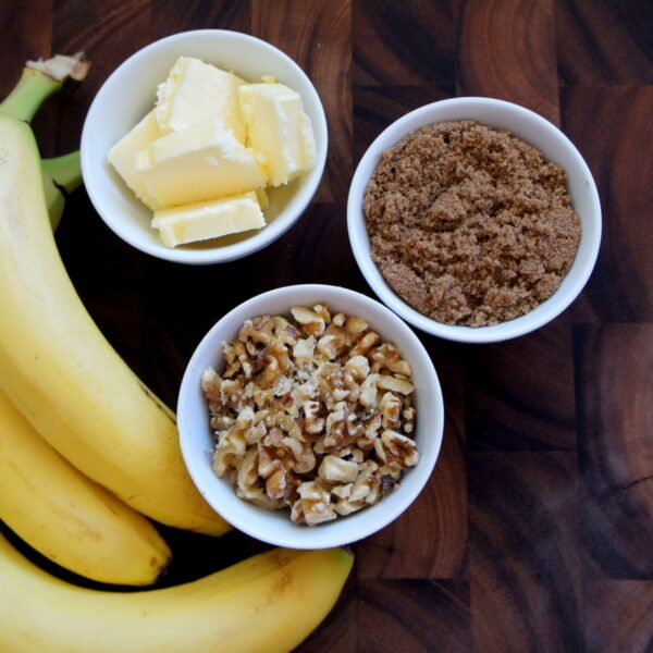 A wooden surface with a bowl of butter slices, a bowl of chopped walnuts, a bowl of brown sugar and 3 bananas next to them