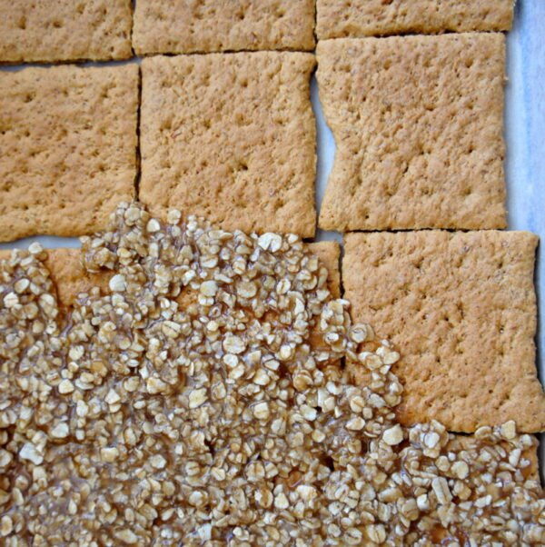 Graham cracker squares being topped with oats and toffee