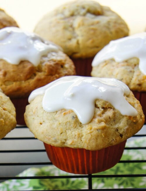 A close up of muffins on a cooling rack topped with white glaze