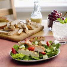 A salad on a plate topped with chicken and strawberry slices and a cutting board of chicken strips in the background