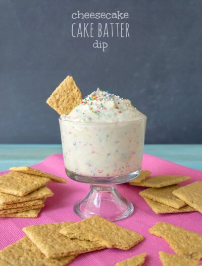 """A desert cup filled with a dip and a graham cracker dipped in it titled, """"Cheesecake Cake Batter Dip"""""""