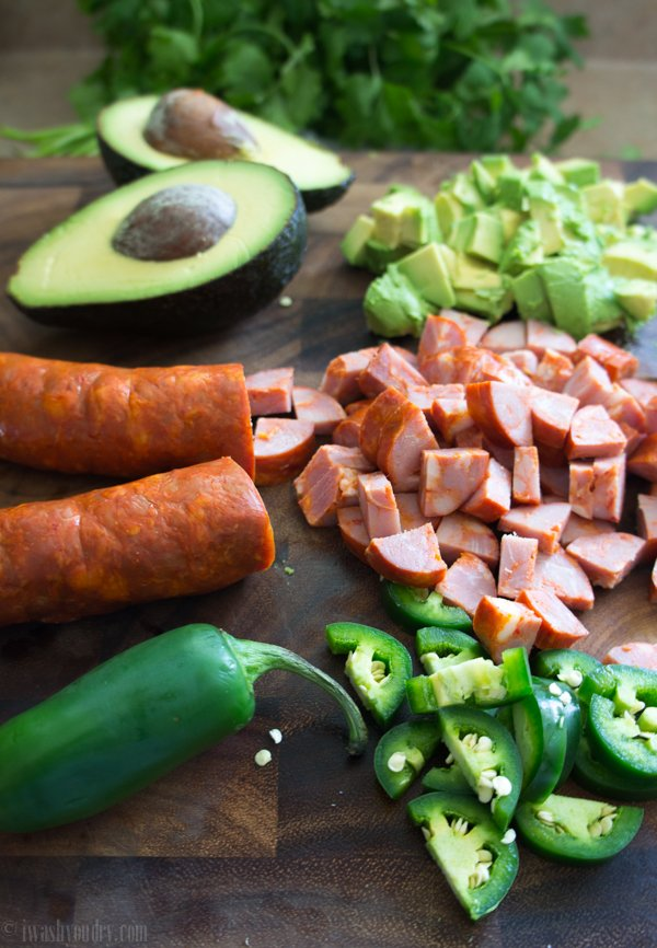 Food on a wooden surface: Chopped avocado, chopped sausage, and chopped Jalapeño