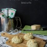 Three biscuits on a wooden cutting board surrounded by tubes of herbs and a block of cheese