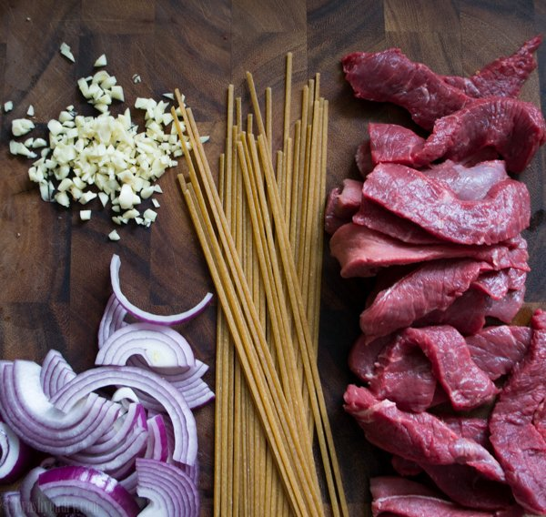 A close up of ingredients on a wooden surface: Minced garlic, onions, dried spaghetti noodles and raw cubbed beef