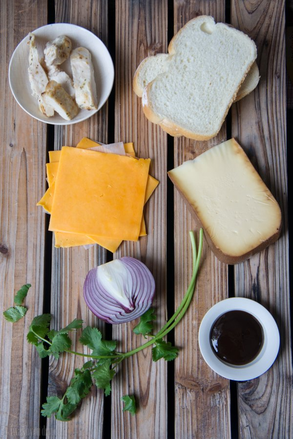 A display of ingredients needed to make BBQ Chicken Grilled Cheese Sandwich: chicken, bread, cheese slices, onion, BBQ sauce