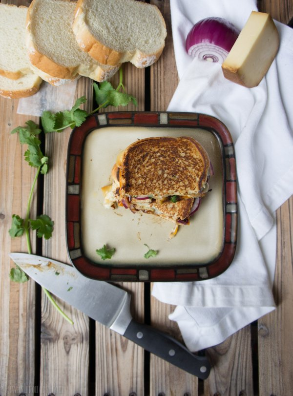 A toasted sandwich on a plate on a wooden surface