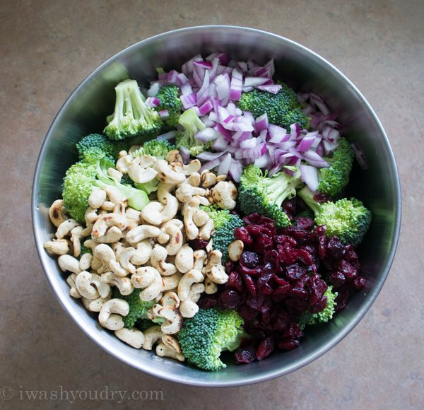 A large bowl with all the ingredients displayed to make Classic Broccoli Salad