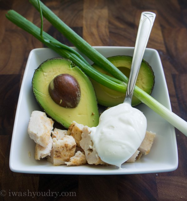 A square white bowl with 2 halves of an avocado, chicken chunks, 2 green onion stalks and a spoonful of Greek Yogurt