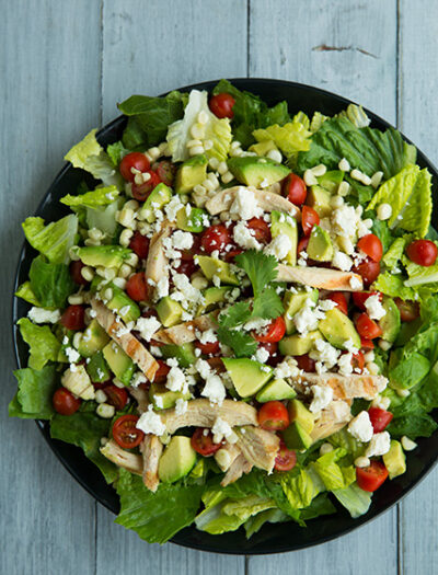 A close up of a salad topped with avocado chunks, veggies and cheese