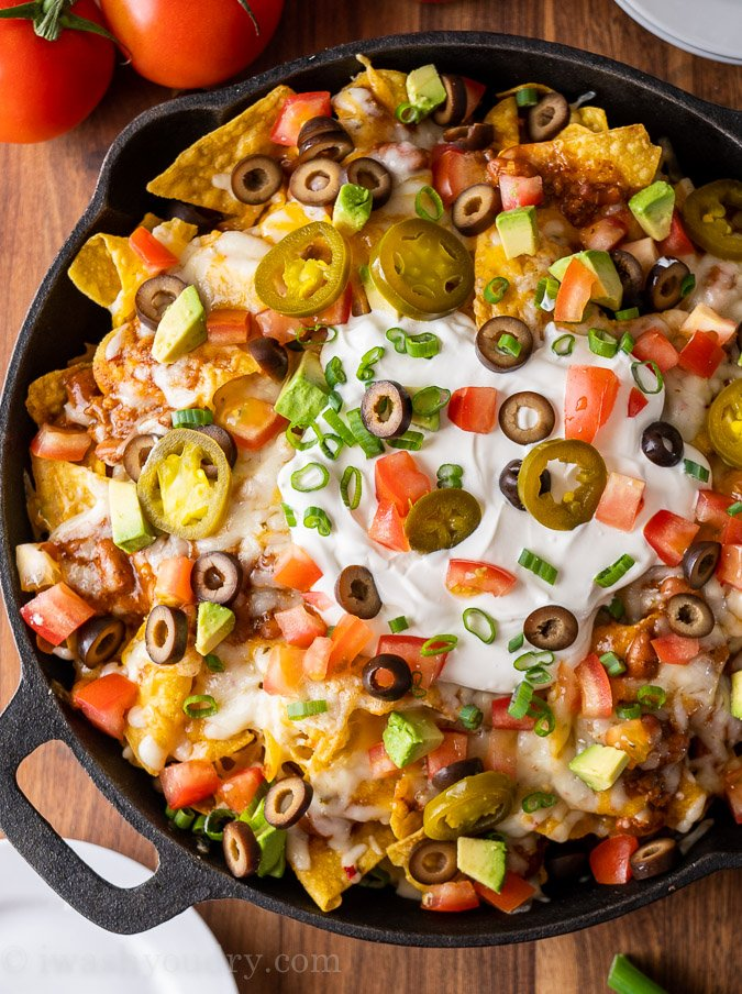 plate of crispy, cheesy nachos with toppings