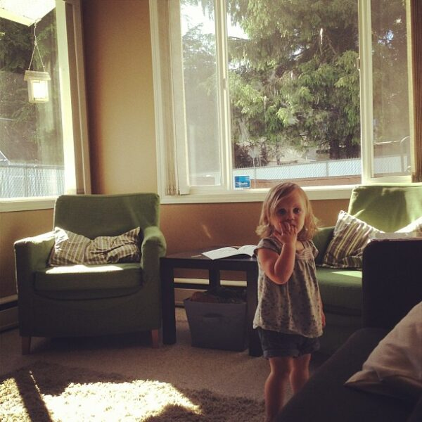A little girl standing in a room next to a couch