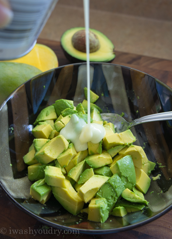 A close up of bowl of avocado chunks with a white liquid being poured on top