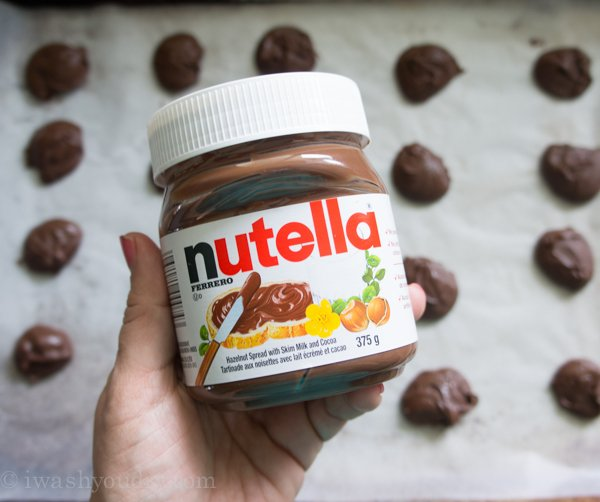 A hand holding a jar of Nutella over a sheet with spaced dollops of Nutella