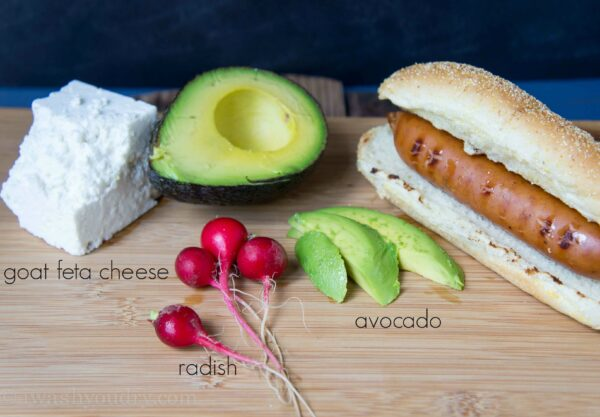A wood surface with radishes, sliced avocado and a Polish dog in a bun