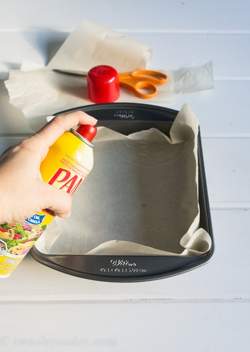 A baking pan lined with parchment paper being sprayed with Pam