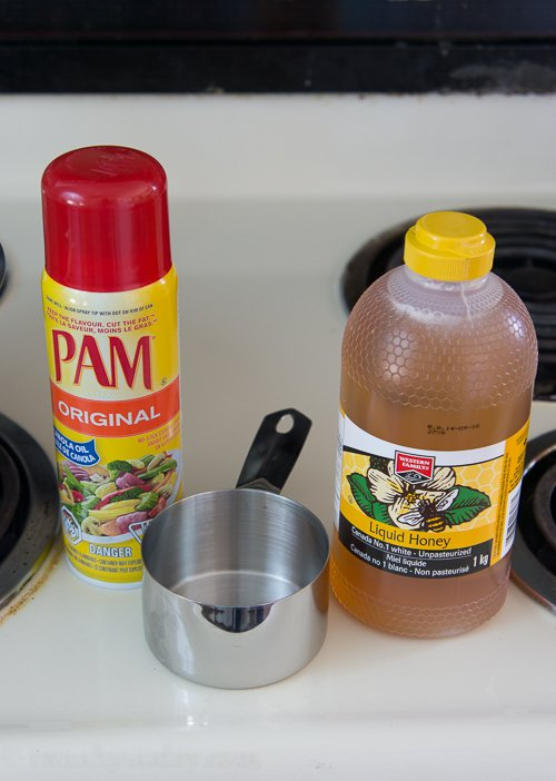 A bottle of Pam spray next to a measuring cup and a jar of honey