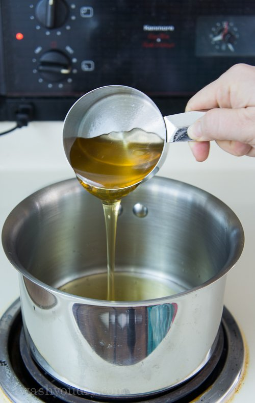 Honey being poured from a measuring cup into a pan
