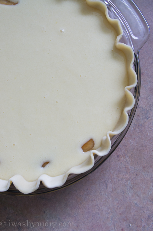 A close up of apple pie streusel base being topped with cake batter