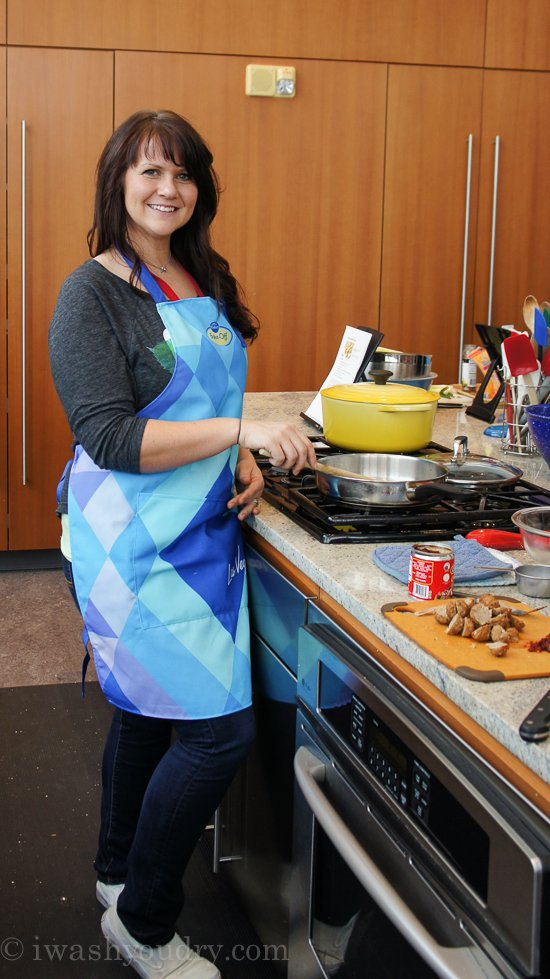 A woman standing at a stove in a kitchen with a pan on the stovetop