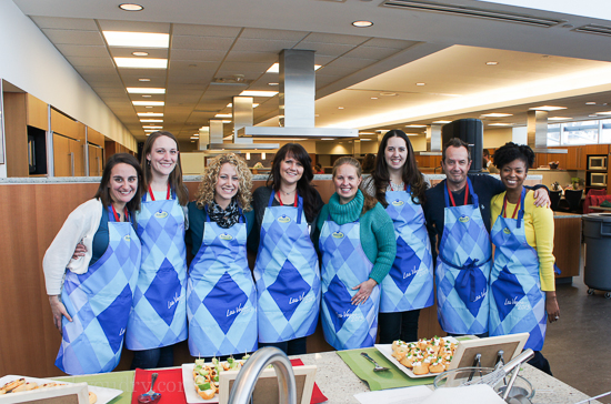 A group of people standing in a line with blue aprons behind a table of prepared food
