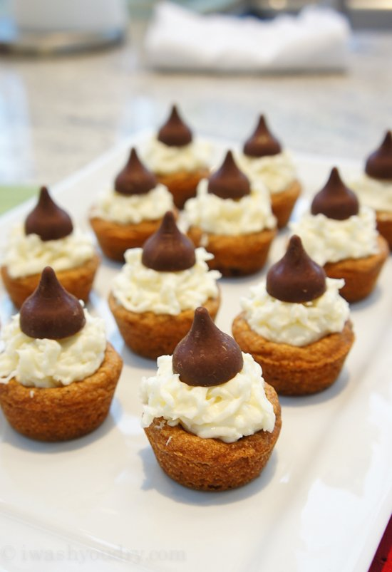 A plate of mini muffin sized cookies topped with whipped cream and a chocolate kiss on top