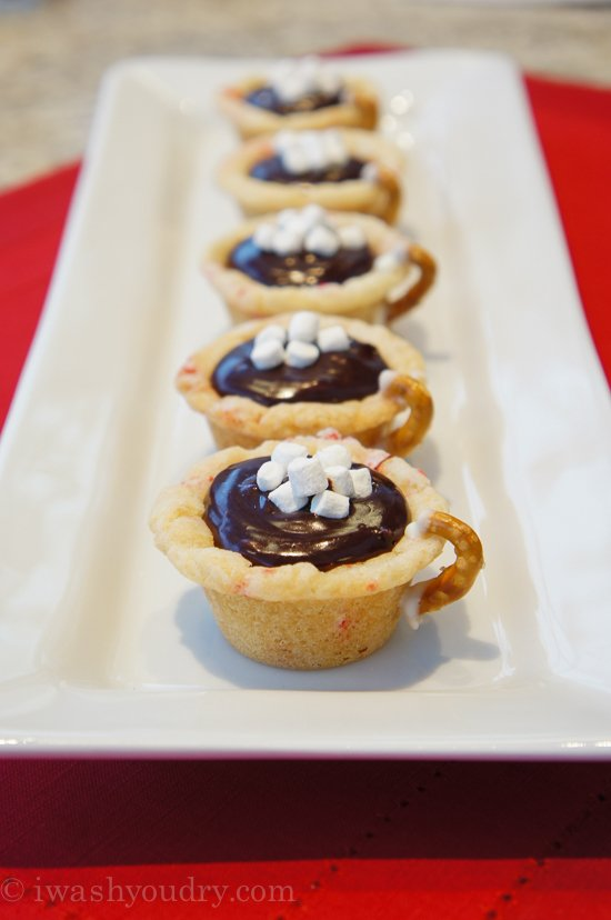 A plate of mini muffin shaped crusts made to look like a mug with chocolate filling topped with mini marshmallows