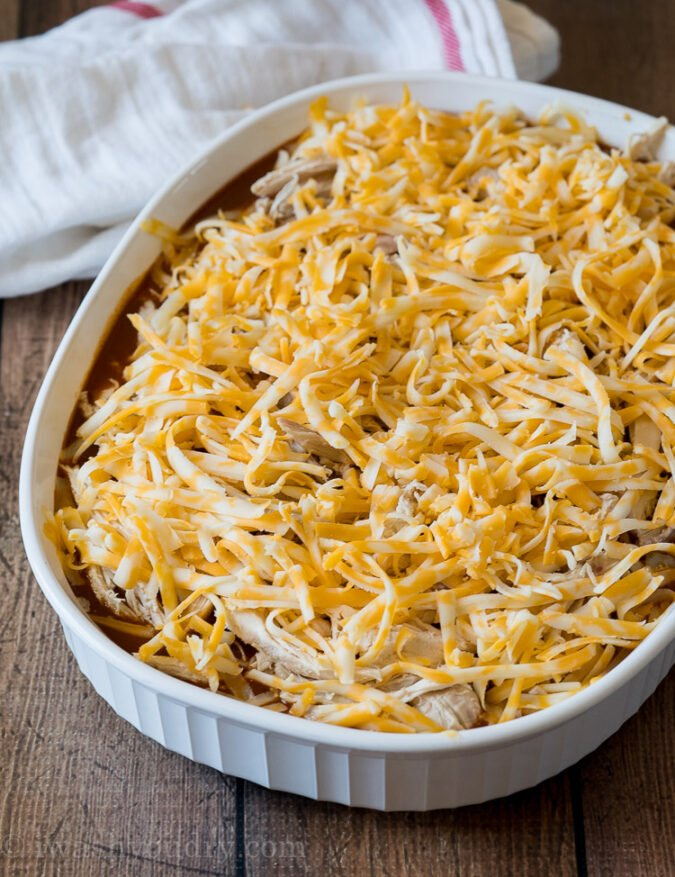 Once the base is done cooking, cover it with enchilada sauce, shredded chicken and lots of cheese, then bake some more.