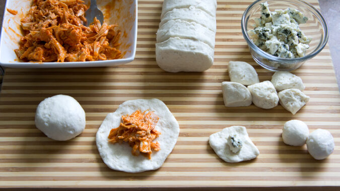 Ingredients displayed for the recipe showing raw dough flattened and shredded chicken in the center