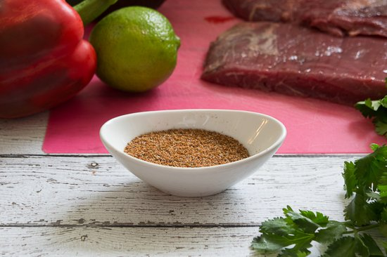 A pictured displaying a spice in a bowl on a wooden surface surrounded by raw carne asada, peppers and lime