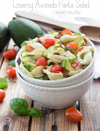 A bowl of salad, with pasta, avocado and tomatoes