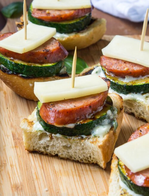 Bread squares with sliced veggies, meat and cheese on top put together with a toothpick.