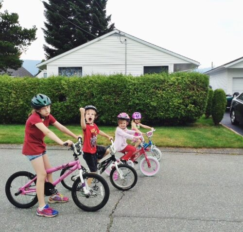 Four kids in the road on bikes riding