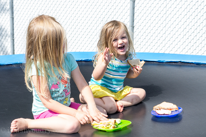 Two little girls eating sandwiches on a trampoline