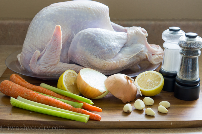 Raw turkey on a pan on a table, surrounded by onions, lemons, carrots and celery