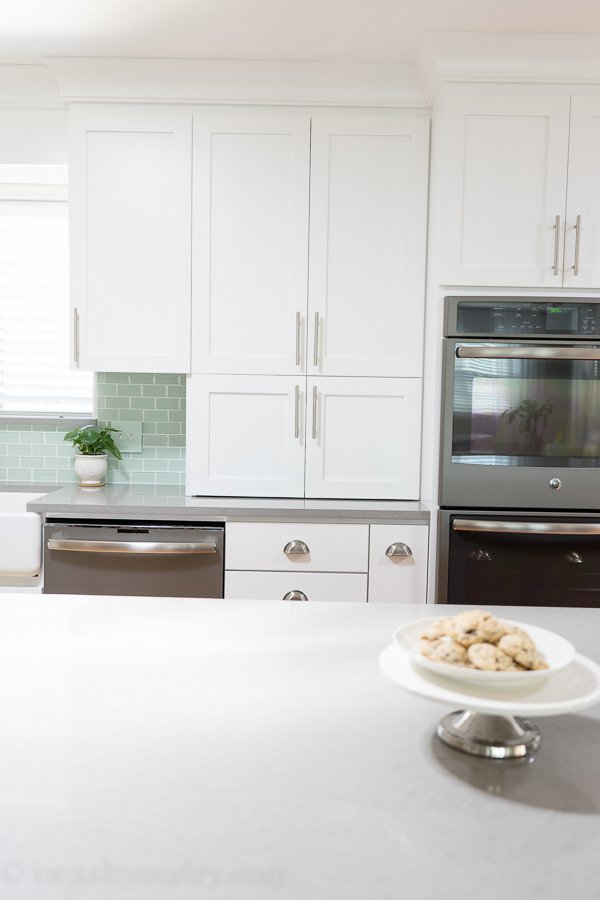 Kitchen Reveal - Love these white shaker-style cabinets with stainless steel cabinet pulls and satin nickel cup pulls.