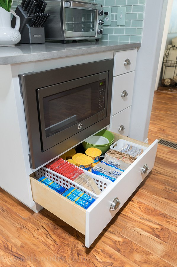 The drawer below the under mount microwave is full of kid approved snacks and meals! This is genius!