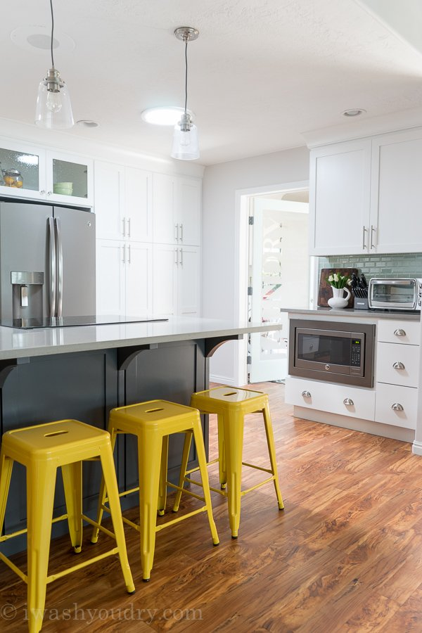 Love the yellow barstools and mini pendant lights above the island! Gorgeous white kitchen with grey slate appliances by GE.