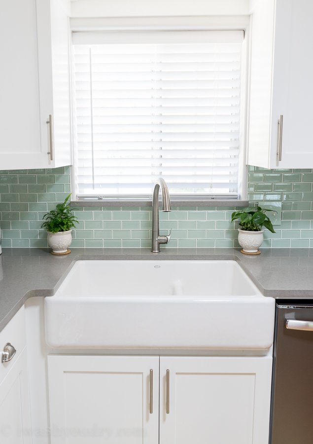 My dream kitchen includes this apron front farm sink with a touchless faucet! Love the backsplash and grey countertops as well. The whole kitchen looks awesome.