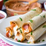 These Pizza Hummus Taquitos are a cheesy, crispy baked snack or appetizer that my kids go nuts for! They're so easy to make too!