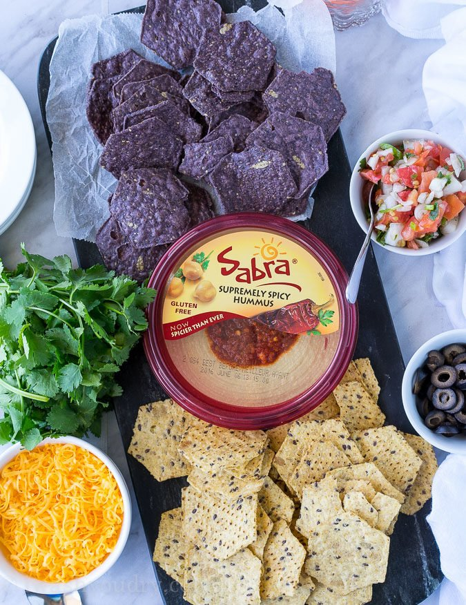 This is by far the easiest way to have your #unofficialmeal. This easy Mexican Layered Hummus Dip starts with a tub of Sabra hummus and is piled high with all the classic taco fillings! So good!