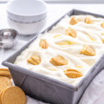 A rectangle pan on a table, with ice cream and vanilla sandwich cookies in it