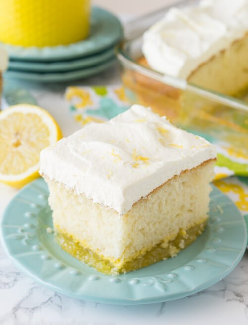 A square of lemon cake on a plate with white frosting